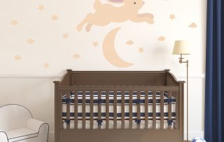 Bunny jumping over moon decal in front of a baby crib.