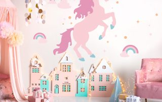 Unicorn wall decal in front of play house in child's play room.