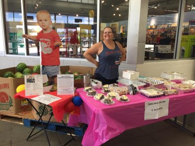 Outdoor bake sale donations table setup with employee and patient ambassador cutout.
