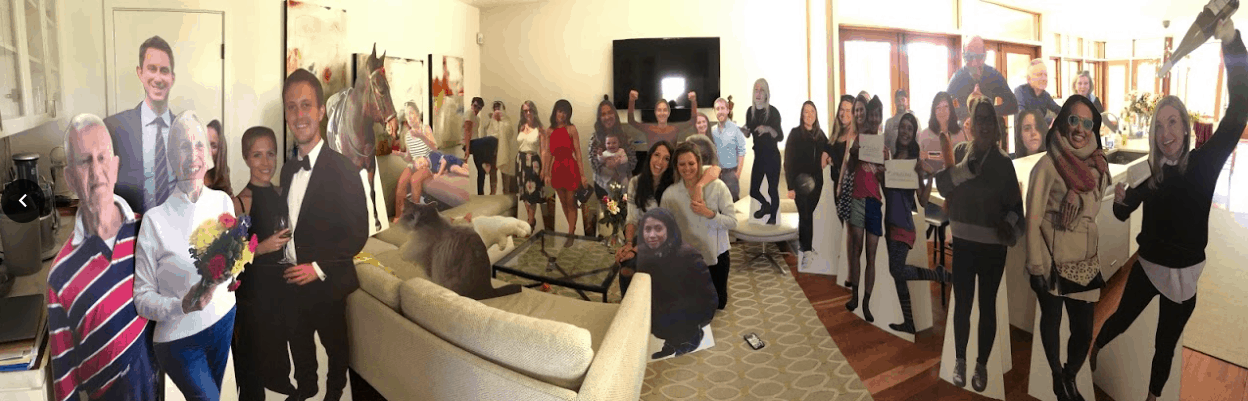 Couple surrounded by life size Cardboard Cutout Standees of friends & family in living room.