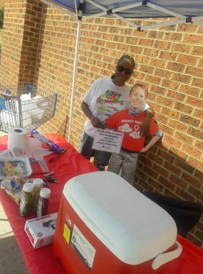 Outdoor donations hot dog cookout table display with employee and patient ambassador cutout.