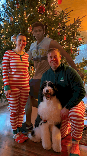 Engaged couple and dog with jogger photobomber cutout and Christmas tree.