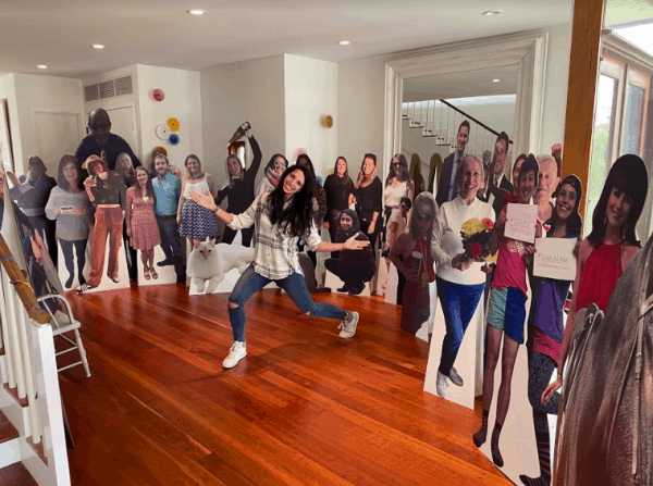 Woman in living room surrounded by life size Cardboard Cutout Standees of friends & family.