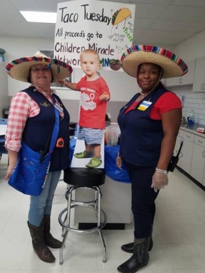 Cutout standee of young patient ambassador boy with 2 WalMart employees and Taco Tuesday sign.