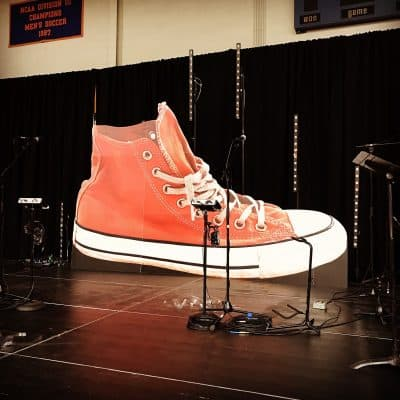 Dare 2 Share large red sneaker cutout on stage display.