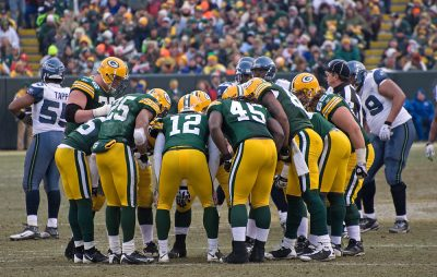 Green Bay Packers huddling led by Aaron Rodgers.
