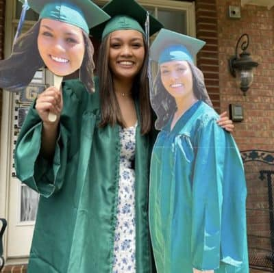 Graduate celebrating with face on a stick and standee.