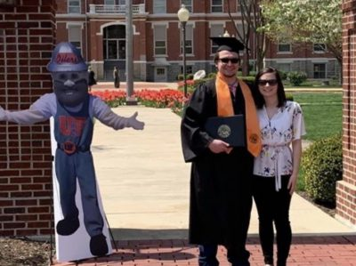 Cardboard cutout of mascot with graduate.