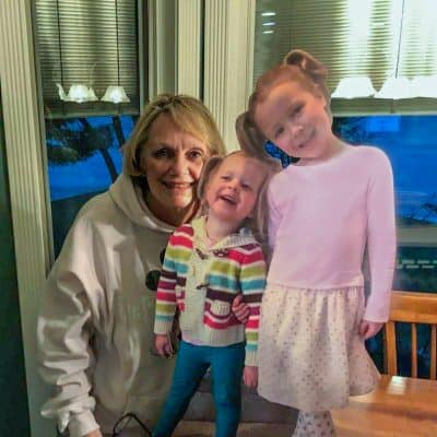 Grandmother with 2 cutouts of her granddaughters.