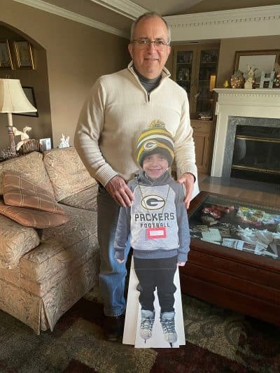 Grandfather with cardboard cutout of grandson.