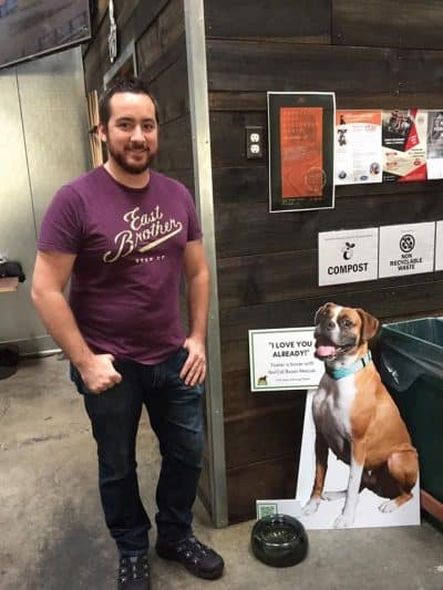 Guy with cardboard cutout of brown and white boxer at East Brother Beer Co.