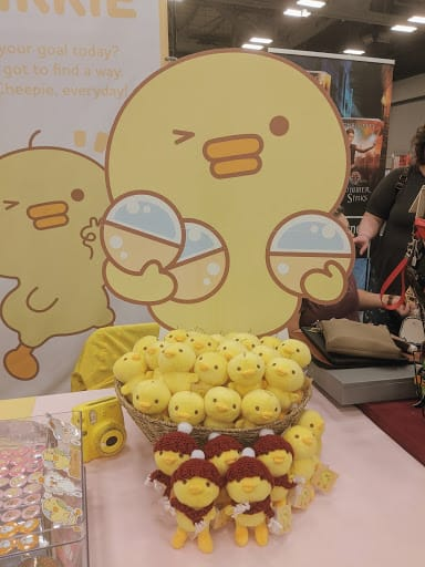 Large KawaiiChikkie cardboard cutout with table display of small stuffed Chikkies.