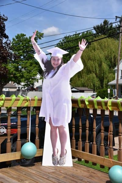 Standee of graduate jumping for joy.