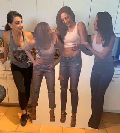 All three daughters in a Mother's Day cardboard cutout.