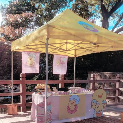 Outdoor table tent setup with KawaiiChikkie cardboard cutout.