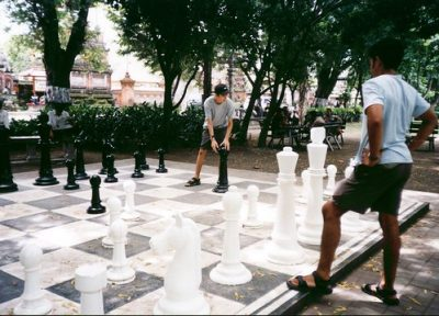2 men play chess on a giant game board in a city park.