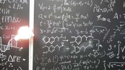 Scientific chalkboard with equations on it.