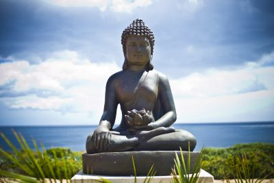 Buddha statue over ocean landscape.