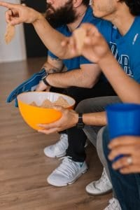 Guys in blue shirts on couch with bowl of chips for Super Bowl party.