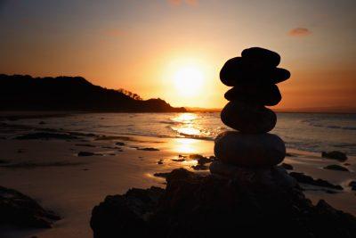 Stacked zen stones on a sunset beach.